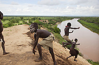 Ethiopia. Southern Nations, Nationalities, and Peoples' Region. Omo Valley. Korcho Village. Kara tribe. Agro-pastoralist group. The Kara men are best known for the elaborate body painting they indulge in before important ceremonies. They paint their faces and bodies in white chalk. A froup of young boys are jumping down the hill towards the Omo river. The Omo Valley, situated in Africa's Great Rift Valley, is home to an estimated 200,000 indigenous peoples who have lived there for millennia. Amongst them are 1,000 to 2,000 Karo who dwell on the eastern banks of the Omo river. Southern Nations, Nationalities, and Peoples' Region (often abbreviated as SNNPR) is one of the nine ethnic divisions of Ethiopia. 8.11.15 © 2015 Didier Ruef