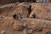 Daytime landscape view of construction workers sitting sitting on the side of a ditch in a construction site in the old part of Dàtóng Shì Chéng Qū in Shānxī Province, China  © LAN