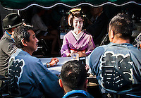 Geisha sitting with male friends outdoors in Tokyo`s Asakusa district during festival.