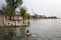 A man bathing in Dongting Lake, Hunan Province. Dongting Lake has decreased in size in recent decades as a result of land reclamation and damming of the Yangtze. China. 2010