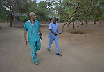 "Dr. Tom Catena (left), a Catholic lay missionary from the United States, walks with a nurse through the grounds of the Mother of Mercy Hospital in Gidel, a village in the Nuba Mountains of Sudan. The area is controlled by the Sudan People's Liberation Movement-North, and frequently attacked by the military of Sudan. The Catholic hospital, at which Catena is often the only physician, is the only referral hospital in the war-torn area. Catena is popularly referred to as ""Doctor Tom"". Behind the two is a foxhole, one of many on the hospital grounds that provides limited shelter during bombings."