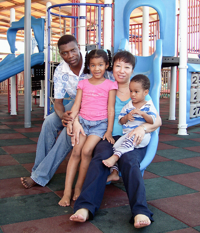 Benin / Cotonou / 7.6.2009 / Abdon Adjalla, 43 years old from Benin, and Shi Yajuan, 36 years old from China, with their 6 year old daughter Syndia, and their 2 year old son Owen, at the Cotonou playground. They met each other in Cotonou, the economic capital of Benin, in 1999.In 2001 they married in Africa, and then repeated the traditional ceremony in China, in Shenyang, Liaoning province, the birthplace of Shi YaJuan. They live in the residential district of the city, the Jacques quarter, and run a shop of imported objects in Cotonou. When they retire, they plan to divide their lives, spending a few months in China, and a few months in Africa. Abdon speaks fluent Chinese: after graduating high school he left for China using a fellowship from the Chinese government, discarding his first choice, Canada. Today there are more and more African students obtaining grants to study Chinese in China. For instance, translators are badly needed: there is a lack of translators which is hurting the communication between both sides.More and more people want to learn Chinese, and the reason is that even if they learn English, the chance to get a U.S. visa would be very low.After the first cold winter Abdon spent in Beijing, he discovered that China could also be a beautiful country, and he ended up staying for a decade. After earning his degree in agronomy, Abdon began working in Shanghai and Hong Kong, before returning to Cotonou and starting a business as a trader. Many African businessmen are not part of the Diaspora in that they don&rsquo;t live in China year-round, but will go there regularly, such as Abdon.Shi Ya Juan, on the other hand, studied at the University of Textiles in Shanghai. Once she finished at age 26, she left for Benin because she had heard and felt that she could create a good business there. And then she met Abdon.<br /> <br /> &copy; Giulia Marchi