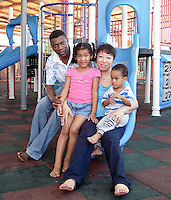 Benin / Cotonou / 7.6.2009 / Abdon Adjalla, 43 years old from Benin, and Shi Yajuan, 36 years old from China, with their 6 year old daughter Syndia, and their 2 year old son Owen, at the Cotonou playground. They met each other in Cotonou, the economic capital of Benin, in 1999.In 2001 they married in Africa, and then repeated the traditional ceremony in China, in Shenyang, Liaoning province, the birthplace of Shi YaJuan. They live in the residential district of the city, the Jacques quarter, and run a shop of imported objects in Cotonou. When they retire, they plan to divide their lives, spending a few months in China, and a few months in Africa. Abdon speaks fluent Chinese: after graduating high school he left for China using a fellowship from the Chinese government, discarding his first choice, Canada. Today there are more and more African students obtaining grants to study Chinese in China. For instance, translators are badly needed: there is a lack of translators which is hurting the communication between both sides.More and more people want to learn Chinese, and the reason is that even if they learn English, the chance to get a U.S. visa would be very low.After the first cold winter Abdon spent in Beijing, he discovered that China could also be a beautiful country, and he ended up staying for a decade. After earning his degree in agronomy, Abdon began working in Shanghai and Hong Kong, before returning to Cotonou and starting a business as a trader. Many African businessmen are not part of the Diaspora in that they don't live in China year-round, but will go there regularly, such as Abdon.Shi Ya Juan, on the other hand, studied at the University of Textiles in Shanghai. Once she finished at age 26, she left for Benin because she had heard and felt that she could create a good business there. And then she met Abdon.<br /> <br /> © Giulia Marchi