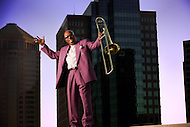 An older african-american man stands on a downtown rooftop with his trombone.
