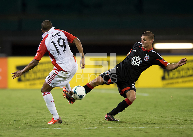 Perry Kitchen (23) of D.C. United takes the ball away from Reggie Lambe (19) of Toronto FC during a game at RFK Stadium in Washington, DC.  D.C. United tied Toronto FC, 1-1.