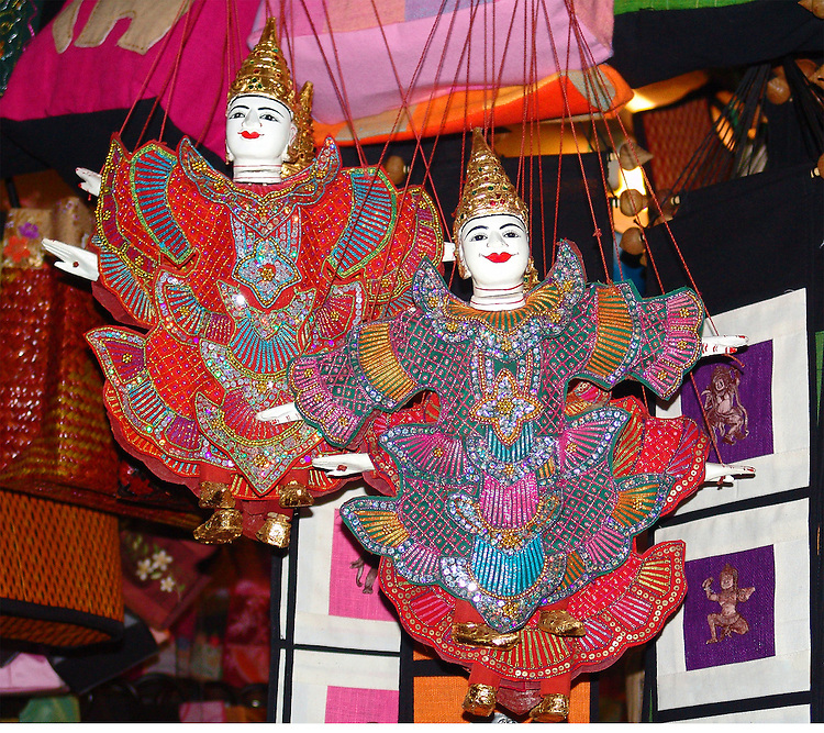 Two marionettes hanging by their strings in a Thai marketplace.They are costumed in red trimed with hot pink and shades of blue and turquoise. Both have the traditional crown, white gloved hands and pointed shoes.