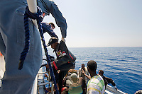 Salvataggio di clandestini provenienti dall'Africa e intercettata al largo dell'isola di Lampedusa..A boat carryng illegal immigrants from Africa is intercepted and rescue by Italian Coast Guard.