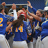 Gianna Azzato #14 of East Meadow gets mobbed by teammates after connecting for a two-run home run in the bottom of the first inning of Game 2 of the Nassau County varsity softball Class AA semifinals against Massapequa at East Meadow High School on Tuesday, May 17, 2016. East Meadow won by a score of 13-6.