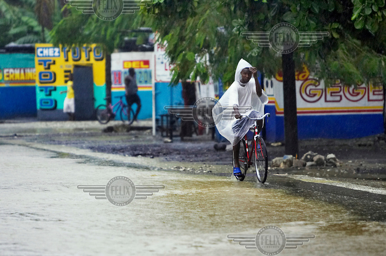 People ride on a bicycle during Hurricane Gustav.