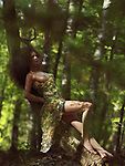 Sensual erotic portrait of a beautiful sexy half nude woman in a summer dress revealing her naked breast and legs lying on a leaning tree trunk in the forest with dreamy romantic expression