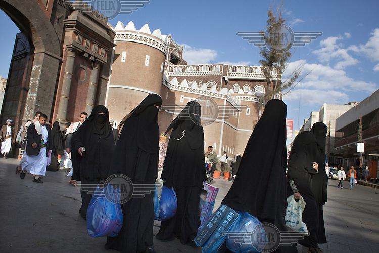 Women walk along a street in Sana'a.