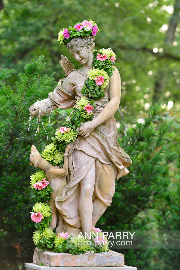 Old Westbury, New York, U.S. 22nd June 2013. Diana the Huntress with her hunting dog is one of many statues decorated with garlands at the Midsummer Night event at Old Westbury Gardens, with dances performed throughout the illuminated grounds of the historic Long Island Gold Coast estate.
