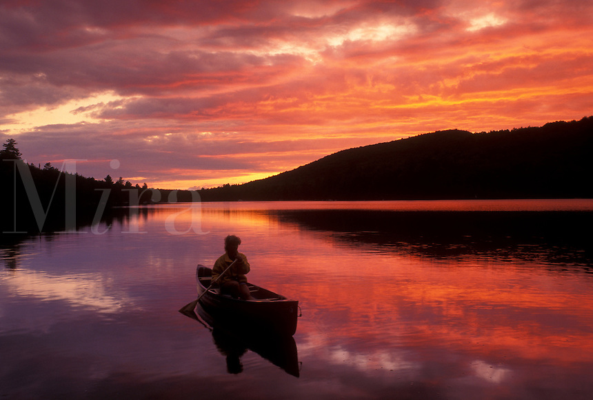 canoeing, canoe, sunset, sunrise, Vermont, VT, Woman paddling a canoe on Kettle Pond at sunset in Groton State Forest.