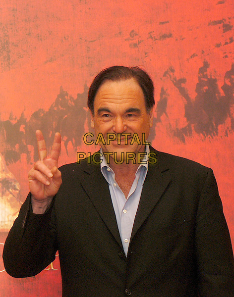 """OLIVER STONE .Photocall for film """"Alexander"""".Hotel St. Regis, Rome, Italy, 10th January 2005.                           .half length director fingers gesture peace sign.Ref: LC.www.capitalpictures.com.sales@capitalpictures.com.©Luca Cavallari/Capital Pictures ."""