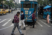 Pedestrians walk to catch the tram and other public transport in Kolkata, West Bengal, India.