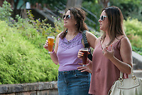 NWA Democrat-Gazette/J.T. WAMPLER Sarah Kilpatrick (RIGHT) and Amy Alexander, both of Fayetteville, walk around the gardens surrounding the Old Post Office Sunday Oct. 7, 2018 at the Arkansas Brewers Guild's Oktoberfest celebration on the Fayetteville Square. The community event feature beer sampling, games and live music. For more information about the Arkansas Brewers Guild visit their Facebook page.
