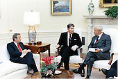 United States President Ronald Reagan discusses the proposed 1990 federal budget with Drew Lewis, left, and Robert Strauss, right, in the Oval Office on Tuesday, January 10, 1989.  Lewis and Strauss are co-chairman of the National Economic Commission..Mandatory Credit: Pete Souza - White House via CNP