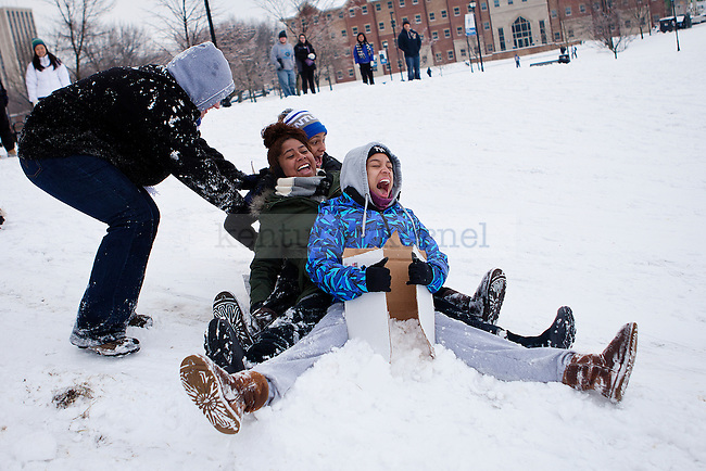 "Sophmores ReDell Atkinson, Julia Vega and Sarah Smith scream while being pushed down the hill on a piece of cardboard in ""the Bowl"" outside William T. Young Library in Lexington, Ky., on Monday, February 3, 2014. Photo by Emily Wuetcher  