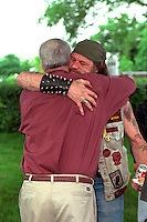 Men age 55 embracing at Vietnam Wall on Memorial Day. St Paul Minnesota USA