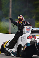 May 17, 2014; Commerce, GA, USA; NHRA funny car driver Tim Wilkerson climbs from his car after exploding an engine during qualifying for the Southern Nationals at Atlanta Dragway. Wilkerson would be uninjured in the explosion. Mandatory Credit: Mark J. Rebilas-USA TODAY Sports