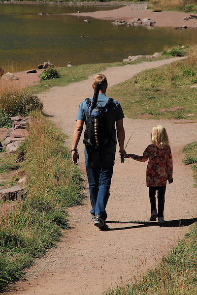 Caucasian father and daughter walking on trail, while fishing at Maroon Lake, Maroon Bells-Snowmass Wilderness Area, west of Aspen, Colorado, USA
