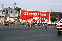 Cina Pechino 1986 traffico di biciclette , grande cartellone rosso sullo sfondo con scritte in cinese<br />