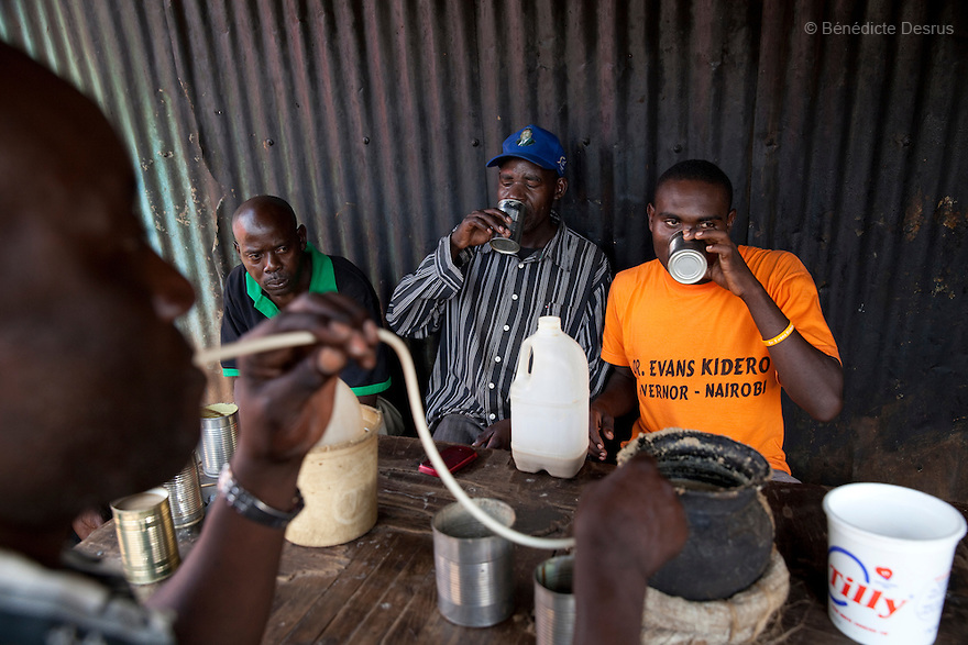 A group of Kenyans men drink Busaa, a traditional fermented beer, from a common pot using long straws - in Gatina Busaa club at midday in a Nairobi slum on April 5, 2013. Busaa is made by crudely fermenting maize, millet, sorghum or molasses. At Kshs 35 per liter it is much cheaper than a Kshs120 half-liter bottle of commercial beer. The local brew was legalised in 2010 and since then Busaa clubs have become increasingly popular in slums and rural areas. Drinking is on the rise in Kenya, especially among young people. Photo by Benedicte Desrus