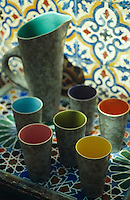 A ceramic jug and matching beakers on a table of patterned tiles
