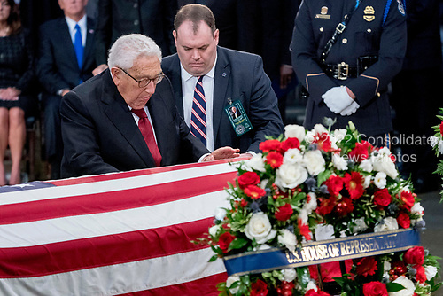 Former Secretary of State Henry Kissinger touches the casket of Sen. John McCain, R-Ariz., as he lies in state in the Rotunda of the U.S. Capitol, Friday, Aug. 31, 2018, in Washington. (AP Photo/Andrew Harnik, Pool)