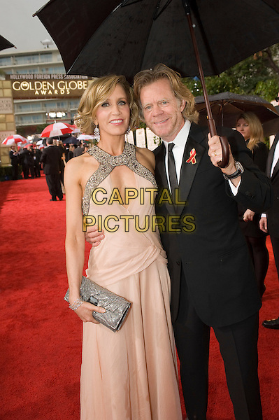 FELICITY HUFFMAN & WILLIAM H. MACY.Arrivals at the 67th Golden Globe Awards held Beverly Hilton, Beverly Hills, California, USA..January 17th, 2010.globes full length husband wife married black suit peach pink dress clutch bag silver umbrella 3/4.CAP/AW/HFPA.Supplied by Anita Weber/Capital Pictures