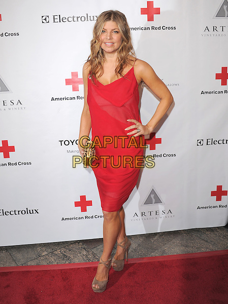 FERGIE (STACY FERGUSON).At The American Red Cross, Santa Monica Chapter's Annual Red Tie Affair held at The Fairmont Miramar Hotel & Bungalows in Santa Monica, California, USA, April 9th 2011..half length  red dress  hand on hip  gold animal leopard print clutch bag     platform shoes sandals  beige heels                                                                          .CAP/RKE/DVS.©DVS/RockinExposures/Capital Pictures.