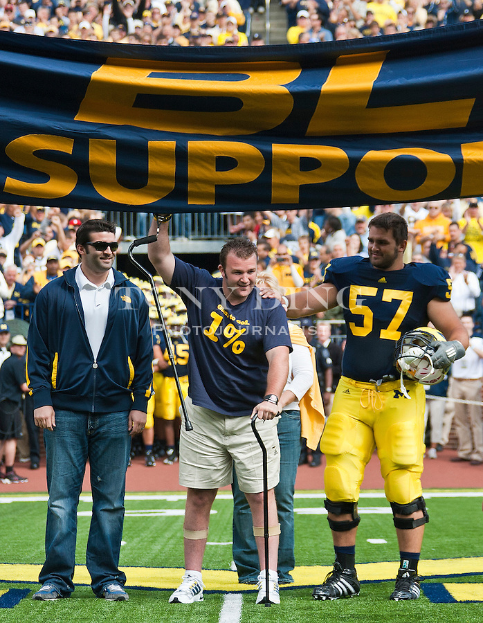 """Brock Mealer, center, with brother and Michigan offensive lineman Elliott Mealer (57), touches the """"Go Blue"""" banner as he led the Michigan football team into Michigan Stadium, before an NCAA college football game with Connecticut, Saturday, Sept. 4, 2010, in Ann Arbor, Mich. Brock Mealer, who suffered a paralyzing car accident in 2008, credits the Michigan football program in aiding his recovery. (AP Photo/Tony Ding)"""