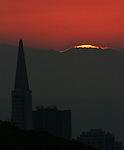 As the morning sun slowly peaks over the horizon during the Transamerican Pyramid marks the skyline of San Francisco, California.