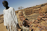 Mr Hammad Arja Hamdan stands in front of his destroyed house in the village of Angala in north darfur on Nov 2004. he and his little daughter left their village in Feb 2004 when the janjaweeds, armed arab militias, completely detroyed it. the genocide began two years ago, since then hundreds of thousands of innocent darfurians were killed and millions have been displaced. athough 200.000 floded into Chad and found help from the international community, the majority still lives in fear in the inner borders in drammatic conditions.