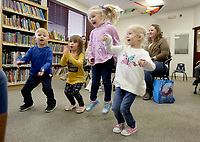 Aedan (cq) Clark, 3, (from left) jumps in the air Tuesday, January 14, 2020, with Macie Dirks, 3, Kimber Cruz, 4,  and Lillie Campbell, 4, as they are asked questions about colors from Joy Poynor, children's services librarian at the Farmington Public Library, during the Little Cardinal's Story Time at the library. The library is currently under expansion that will add about 1,000 square feet that will include a meeting and study room and a remodel of the the children's, teen and adult areas. Check out nwaonline.com/200115Daily/ and nwadg.com/photos for today's photo gallery.<br /> (NWA Democrat-Gazette/David Gottschalk)