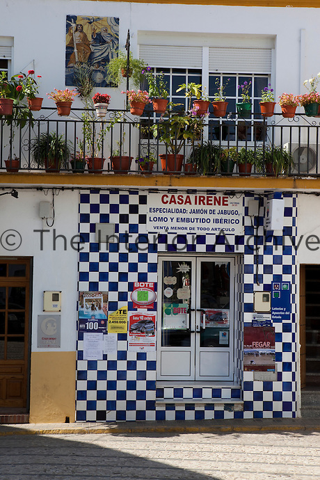 Exterior of a blue and white tiled shop specializing in the sale of jamon de jabugo, the local speciality of Aracena, Andalucia