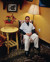 A doctor poses for his portrait in his own waiting room.  Mexico City 3-10-04