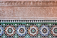 Carved stucco decoration and zellige tiles from courtyard of Ben Youssef Madrasa, Medina, Marrakech, Morocco. The stucco is carved in an Iraqi kufic style of calligraphy with interwoven vegetal design. Below is zellige tilework, terracotta tiles covered with 5 colours of enamel and set into plaster, typical of the Hispano-Moresque period. The Madrasa is an Islamic theological college founded in the 14th century and rebuilt by the Saadians in the 1560s. It is named after the Almoravid Sultan Ali ibn Yusuf, who reigned 1106-42. Picture by Manuel Cohen