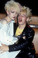 August 1981. Newcastle area, England. During this time the Punk movement begins, and tattoos, piercings, and colorful hair become popularized. At the same time the Romantic movement is born, and makeup, black and white clothing are the typical fashion seen at night clubs and dance parlors. People of the Romantic movement gather for parties at night clubs.