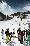USA, Colorado, Aspen, skiers at the base of Aspen Mountain Ski Resort with the gondola in the distance, Ajax