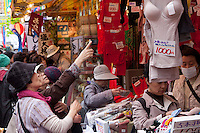 Older Japanese women shopping for the famous and iconic red underwear, that is supposed to bring health to the wearer on Jizo Dori shopping street in Sugamo, Tokyo, Japan Wednesday, April 14th 2010. Sugamo is affectionately known as the old lady Harajuku, in reference to the Mecca for youth fashions in the South of Tokyo, and is a popular place for Tokyo's increasingly aged population.