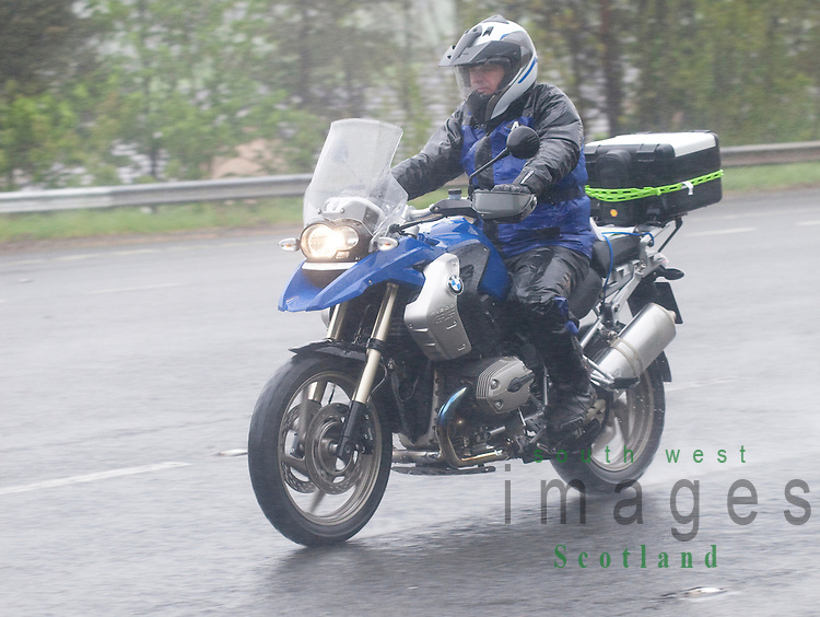 Dual carriageway road A75 near Dumfries Scotland UK bad weather rain mist spray motorbike with a wet motorcyclist heading for North West 200