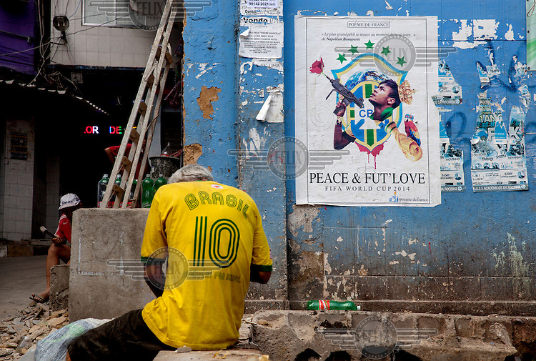 A man wearing a Brasil football shirt sits beside a poster produced for the FIFA 2014 World Cup in the Rocinha favela.