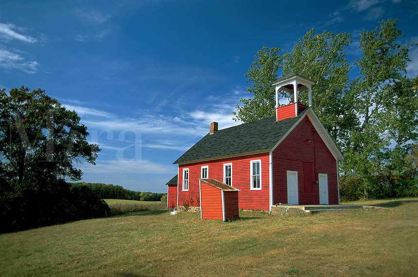 A little, red one-room schoolhouse sits on a grassy hill under a wide blue sky. Minnesota.