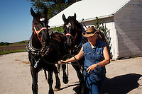 Wellsville, Kansas, May 28, 2011 -  Fourth generation family farmer Robin Dunn  loads her draft horses in preparation for  the annual Cottonwood Mini Masters, an event hosted by Cottonwood Inc. which provides services for mentally and physically challenged adults. Dunn provides wagon rides for the event every year. ..Dunn bought her great grandparents homestead from her father in 1993, and today grows soybeans, corn, sorghum and hay, and maintains a small herd of Black Angus cattle and eight horses which she uses to for wagon and stage coach rides.  According to the most recent Department of Agriculture data, there are more than 306,000 farms run primarily by women in 2007, representing about 14 percent out of the 3.3 million American farms.  That's up from 237,819 or 11 percent in 2002, and a big increase from the 1980s when about five percent of U.S. farms were operated by women. Dunn has branched out from her farming business, using her century-old dairy barn to host 25 to 30 weddings and other events a year. She also attracts tourists for farm tours and carriage rides, and holds sessions with school children to teach them about faming.