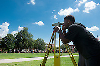 Cory Qualls, a junior civil engineering major from Scott County, surveys the Drill Field as students pass by. The surveying lesson was part of a class in MSU's Department of Civil and Environmental Engineering. <br />  (photo by Megan Bean / &copy; Mississippi State University)