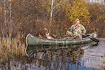 Crossbow hunter and 8-point white-tailed buck in a canoe.