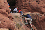 Father follows family climbing rock wall in Arches National Park, Moab, Utah, USA. .  John offers private photo tours in Arches National Park and throughout Utah and Colorado. Year-round.