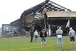 Foto: VidiPhoto<br /> <br /> ERICHEM &ndash; De brandweer is vrijdag nog lange tijd bezig geweest met het nablussen van de enorme brand in de stallen van De Knorhof aan de Erichemsewal in Erichem, bij Tiel. De brand is volgens de brandweer ontstaan in een stal achter het woonhuis. De oorzaak is nog niet bekend. Door niet ge&iuml;mpregneerde isolatiepanelen en de zogenoemde luchtwassers, die stank in de omgeving tegengaan, verspreidde de brand zich razendsnel door alle stallen. Binnen een half uur was het vuur verspreid door het hele complex. Daarbij kwamen 16.000 varkens om. Het bedrijf heeft vergunning voor 20.000 varkens. Het enorme complex telt ongeveer 120 bij 120 meter. Bij de brand is asbest in de directe omgeving vrijgekomen. Een extern bedrijf brengt het verspreidingsgebied in kaart. Verderop in het dorp zijn roetdeeltjes neergedaald. De brand in Erichem is de grootste varkensbrand ooit in ons land. Foto: Personeel van het bedrijf aanschouwt de ravage.