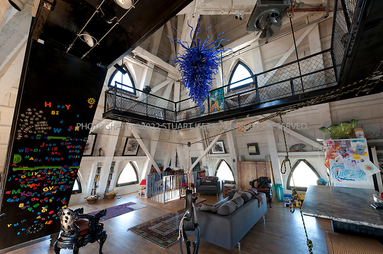 9/27/2010--Seattle,WA, USA..The main living room, kitchen and dining room on the second floor of Petra Franklin's penthouse apartment in Smith Tower in Seattle, complete with Dale Chihuly chandelier...Smith Tower, located in Seattle's Pioneer Square neighborhood, is the oldest skyscraper in the city. Completed in 1914 it has 38 floors and  remained the tallest building on the West Coast until the Seattle Space Needle overtook it in 1962. The tower is 462 ft (143 meters) from street level to the top of the pyramid with a small glass lighthouse at the top...Petra Franklin, 46 and her husband David Lahaie, 51 live in the pyramid on top of Smith Tower with their two daughters Simone, 6, and Naomi, 3. Franklin is co-founder and general partner of Vault Capital, a venture capital fund with offices in Smith Tower...Copyright © 2010 Stuart Isett. All rights reserved.